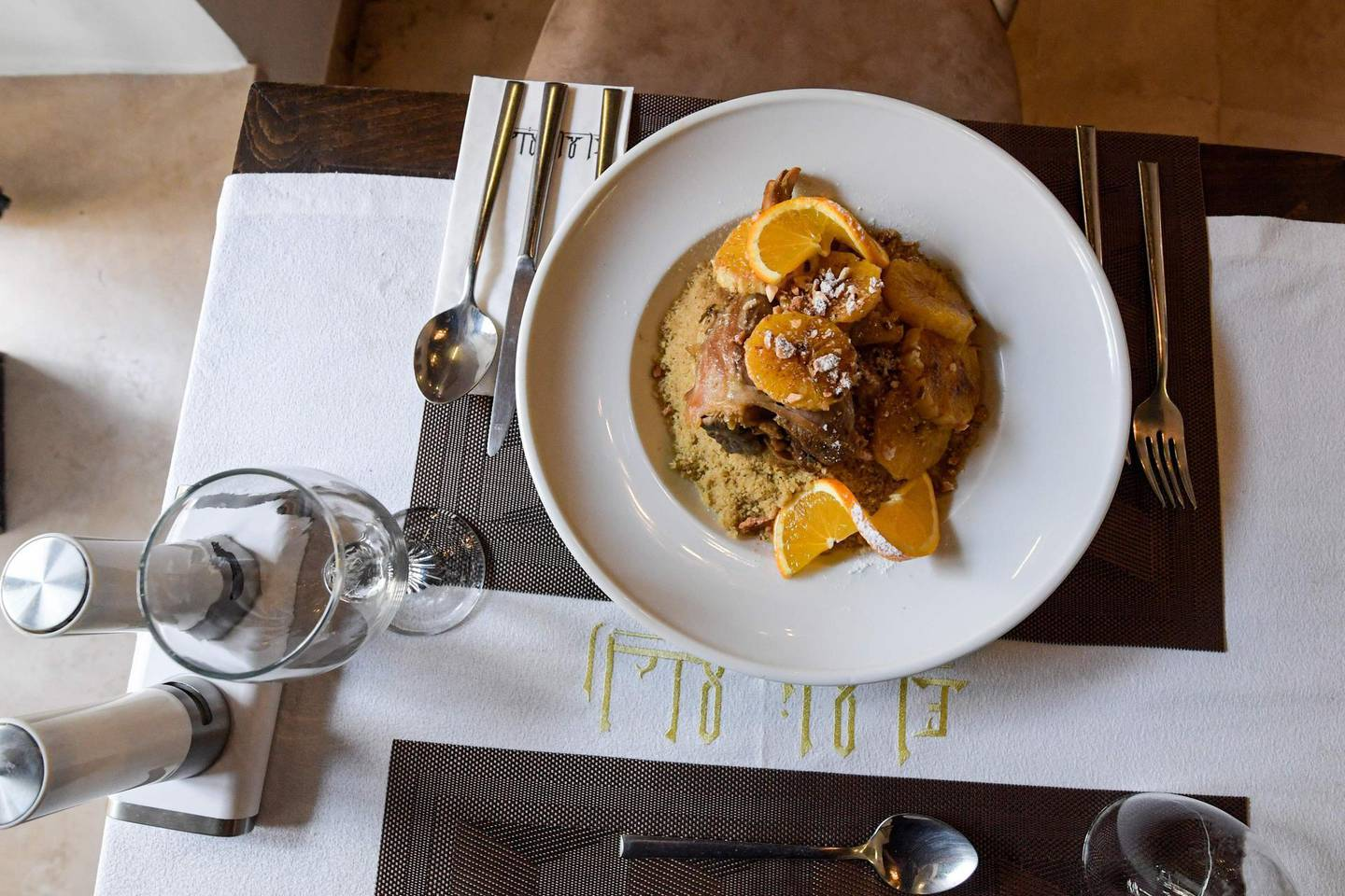 This picture taken on December 16, 2020 shows a view of a dish of lamb and orange couscous prepared by Tunisian chef Taieb Bouhadra, at a restaurant in the Medina (old town) of Tunisia's capital Tunis. Couscous, the Berber dish beloved across northern Africa's Maghreb and Sahel regions, has become a global foodie favourite now found on the shelves of organic supermarkets everywhere. Love it or hate it, but on December 16 the grain staple passed another culinary milestone when the UN cultural organisation honoured it as part of the world's intangible cultural heritage. / AFP / Fethi Belaid