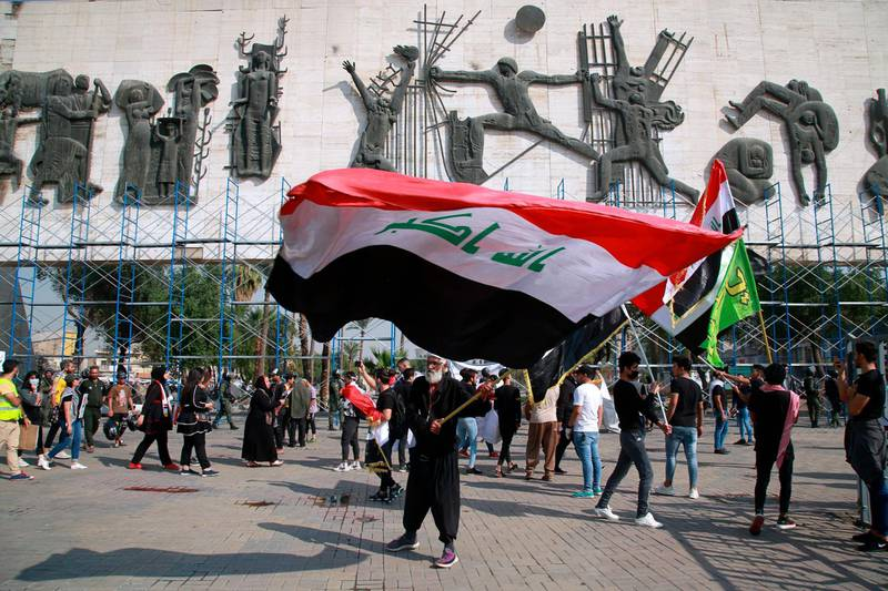A protester waves a large Iraqi flag in Tahrir Square during a demonstration calling for the government to resign, in Baghdad, Iraq, Sunday, Nov. 15, 2020. (AP Photo/Khalid Mohammed)
