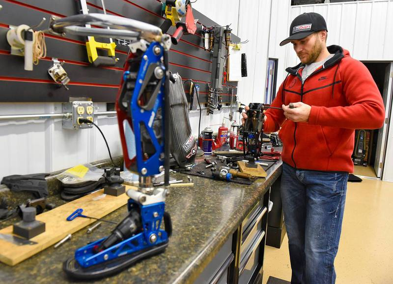 FILE - In this Dec. 22, 2017, file photo, Mike Schultz, who is preparing to compete in the 2018 Winter Paralympics in South Korea and is owner of BioDapt, works on a performance prosthetic for an athlete in his shop in St. Cloud, Minn. (Jason Wachter/St. Cloud Times via AP, File)