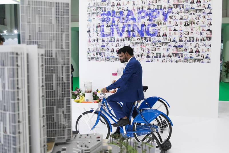 ABU DHABI, UNITED ARAB EMIRATES - April 16 2019.  A man cycles and powers a juice mixture at Tamouh's booth at Cityscape Abu Dhabi 2019.  (Photo by Reem Mohammed/The National)  Reporter: Gillian Duncan Section: NA + BZ