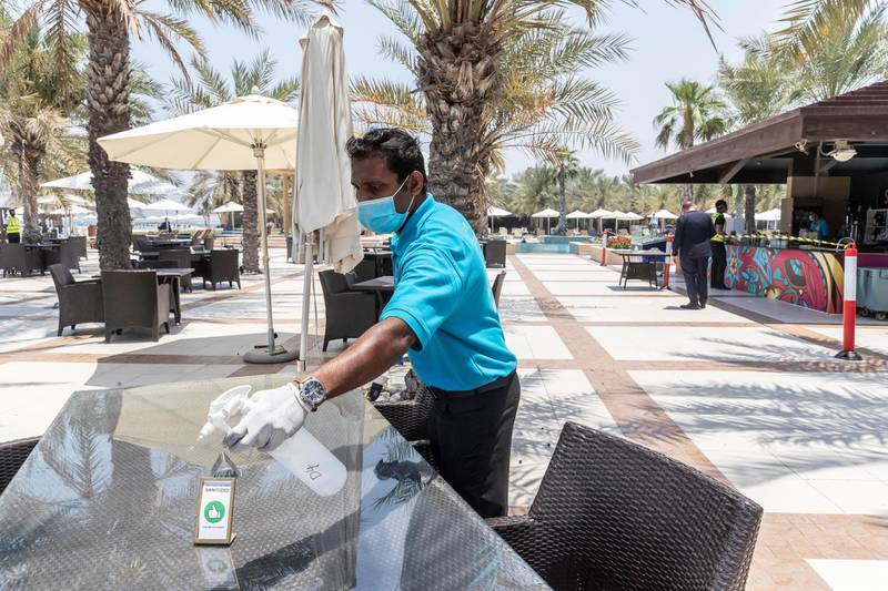 RAS AL KHAIMAH, UNITED ARAB EMIRATES. 21 MAY 2020. A tour with RAK Tourism Development Authority inspectors to know more about Hilton Ras Al Khaimah  Resort & Spa's preventive and hygiene measures as they open up after the hotel lockdown. A table at the beach restaurant is sanitized after each guests to prevent the possible spread of COVID-19. (Photo: Antonie Robertson/The National) Journalist: Ruba Haza. Section: National.