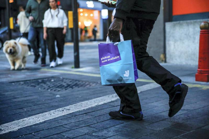 A takeaway food courier, working for Deliveroo, operated by Roofoods Ltd., walks with a customer's food order in London, U.K., on Tuesday, Sept. 29, 2020. Covid-19 lockdown enabled online and app-based grocery delivery service providers to make inroads with customers they had previously struggled to recruit, according the Consumer Radar report by BloombergNEF. Photographer: Hollie Adams/Bloomberg via Getty Images