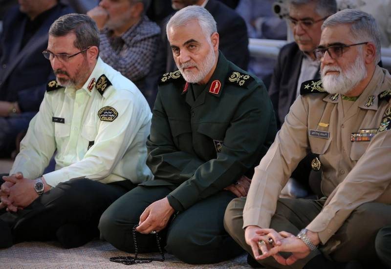 """(FILES) In this file handout picture provided by the office of the Iranian Ayatollah Ali Khamenei on June 4, 2019 shows Iranian Major General in the Islamic Revolutionary Guard Corps (IRGC) Qasem Soleimani (C) listening to the Iranian supreme leader as delivers a speech on the occasion of the 30th death anniversary of the founder of the Islamic republic Ayatollah Ruhollah Khomeini, at his shrine in Tehran. One year after US forces assassinated Iran's top commander in Baghdad, tensions are boiling between Iraq's Washington-backed premier and pro-Tehran forces that accuse him of complicity in the drone strike. US President Donald Trump sent shock waves through the region with the January 3, 2020 targeted killing of Iran's revered General Qasem Soleimani and his Iraqi lieutenant, which infuriated the Islamic republic and its allies. -  === RESTRICTED TO EDITORIAL USE - MANDATORY CREDIT """"AFP PHOTO / HO / KHAMENEI.IR"""" - NO MARKETING NO ADVERTISING CAMPAIGNS - DISTRIBUTED AS A SERVICE TO CLIENTS ===    / AFP / IRANIAN SUPREME LEADER'S WEBSITE / HO /  === RESTRICTED TO EDITORIAL USE - MANDATORY CREDIT """"AFP PHOTO / HO / KHAMENEI.IR"""" - NO MARKETING NO ADVERTISING CAMPAIGNS - DISTRIBUTED AS A SERVICE TO CLIENTS ==="""