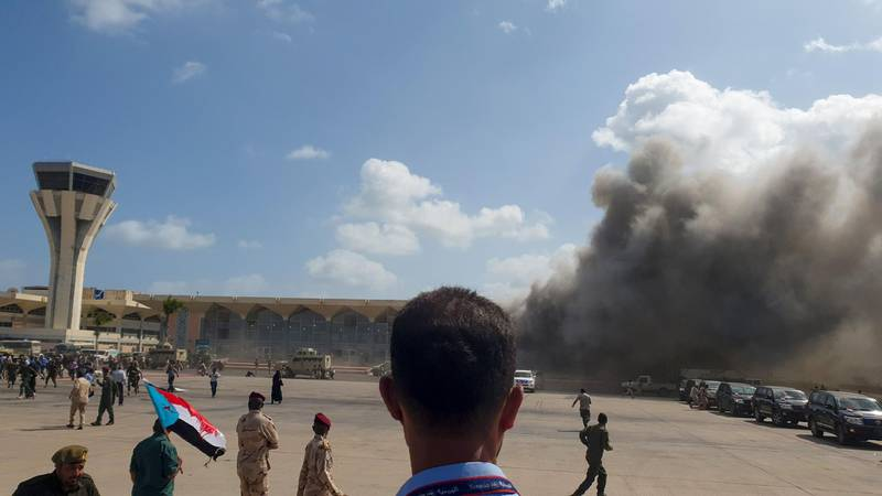 """TOPSHOT - Smoke billows at the Aden Airport on December 30, 2020, after explosions rocked the Yemeni airport shortly after the arrival of a plane carrying members of a new unity government. Explosions rocked Yemen's Aden airport on Wednesday shortly after the arrival of a plane carrying members of a new unity government, an AFP correspondent at the scene said. """"At least two explosions were heard as the cabinet members were leaving the aircraft,"""" the correspondent said. Yemen's internationally recognised government and southern separatists formed a new power-sharing cabinet on December 18,  and arrived in the southern city of Aden on Wednesday, days after being sworn in Saudi Arabia. / AFP / Saleh Al-OBEIDI"""