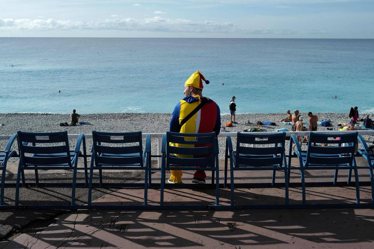 """A man dressed in a clown's outfir looks on as he sits on the """"Promenade des angalais"""" along the Mediterranean sea, in the French riviera city of Nice, on September 29, 2020. / AFP / Valery HACHE"""