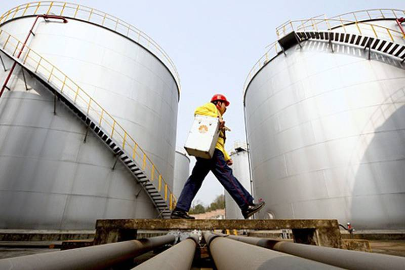 FILE - In this Thursday, Jan. 28, 2010 file photo, a worker walks past tanks at a Petrochina storage base in Suining, in southwest China's Sichuan province. A big shift is happening in Big Oil: an American giant now ranks second to a Chinese upstart. Exxon Mobil is pumping less oil than PetroChina, a company formed just 13 years ago by the Chinese government to better compete for the world's oil and natural gas. On March 29, 2012, the shift is expected to become official when the Beijing company announces that it produced more crude last year than its 130-year-old Texas rival. (AP Photo) *** Local Caption ***  CORRECTION Big Oil New No 1.JPEG-0d101.jpg