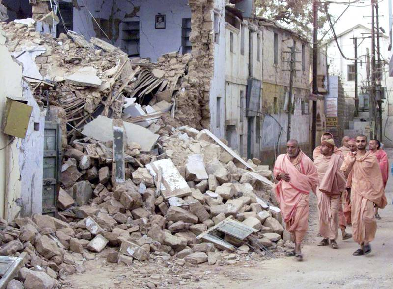 A group of monks walk past rubble on a street in the western Indian city of Bhuj on January 27, 2001, after a powerful earthquake killed tens of thousands in the region. As many as 15,000 people may have died in the massive quake which struck on Friday, the Indian Defence Minister was quoted as saying.  PK/JD