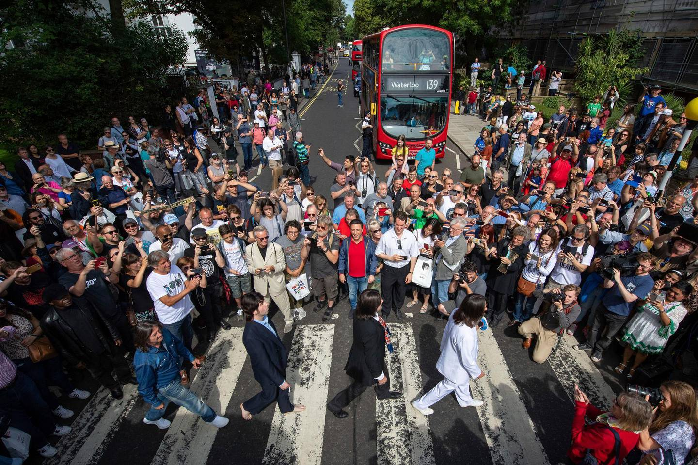 Beatles lookalikes are joined by thousands of fans gathered to walk across the Abbey Road zebra crossing, on the 50th anniversary of British pop musicians The Beatles doing it for the cover of their album 'Abbey Road' in St Johns Wood in London, Thursday, Aug. 8, 2019. They aimed to cross 50 years to the minute since the 'Fab Four' were photographed for the album.(Dominic Lipinski/PA via AP)