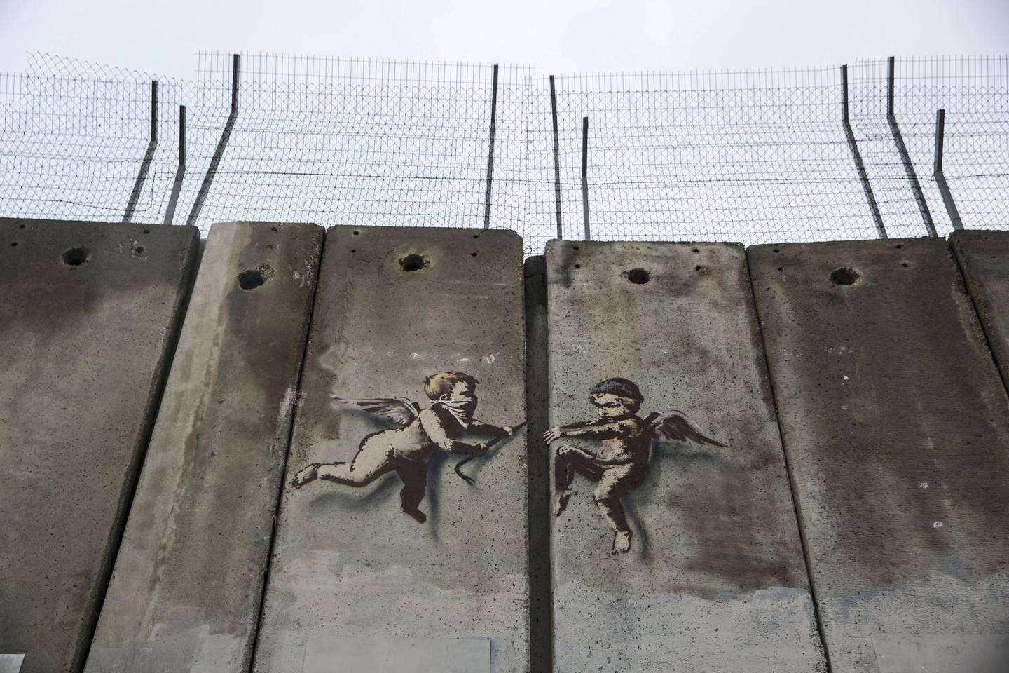 """Street artist Banksy work from last Christmas season on the 8 meter high separation wall built by Israel by his """"Walled Off Hotel"""" in Bethlehem.The angels are painted where by a slight gap, and appears that as if the two angels on either side of the gap, breaking through the wall.(Photo by Heidi Levine for The National)."""