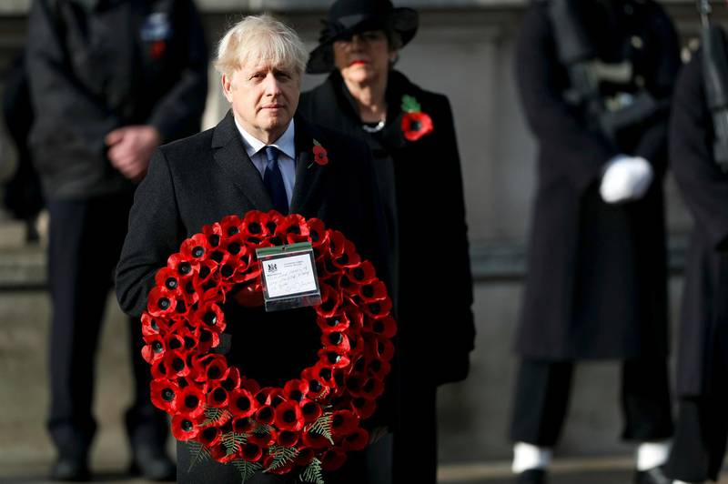 FILE - Britian's Prime Minister Boris Johnson carries a wreath, during the Remembrance Sunday service at the Cenotaph, in Whitehall, London, Sunday Nov. 8, 2020. Johnson says Britain and the United States will work together to support democracy and combat climate change. He denies that his close ties to President Donald Trump would hurt U.K.-U.S relations once President-elect Joe Biden takes office in January.  (Peter Nicholls/Pool Photo via AP, File)