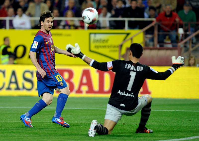 Barcelona's Argentinian forward Lionel Messi (L) scores against Sevilla's goalkeeper Andres Palop (R) during the Spanish League football match Sevilla vs FC Barcelona on March 17, 2012 at Ramon Sanchez Pizjuan stadium in Sevilla.   AFP PHOTO / CRISTINA QUICLER (Photo by CRISTINA QUICLER / AFP)