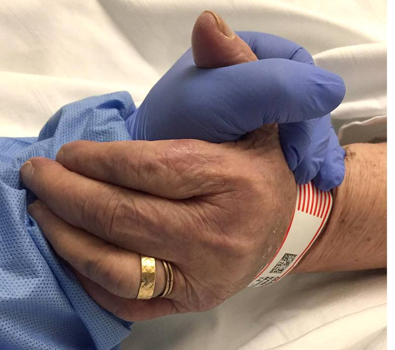 Erkan Nabi holds his mother, Munuse Nabi's hand, in King George Hospital before she died from coronavirus disease (COVID-19), in Ilford, Britain, April 19, 2020.  To match Special Report HEALTH-CORONAVIRUS/BRITAIN-ELDERLY   Erkan Nabi/Handout via REUTERS    THIS PICTURE HAS BEEN SUPPLIED BY A THIRD PARTY.