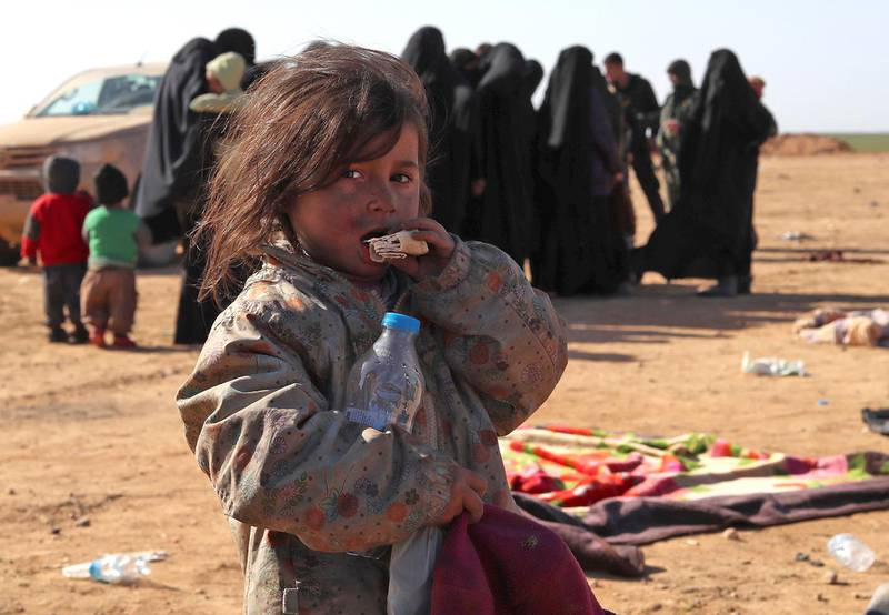 A child nibbles on a piece of bread as civilians fleeing from fighting between Syrian Democratic Forces (SDF) and Islamic State (IS) jihadists in the frontline Syrian village of Baghuz, await to be screened and registered by the SDF in the countryside of the eastern Syrian Deir Ezzor province on January 31, 2019. (Photo by Delil SOULEIMAN / AFP)