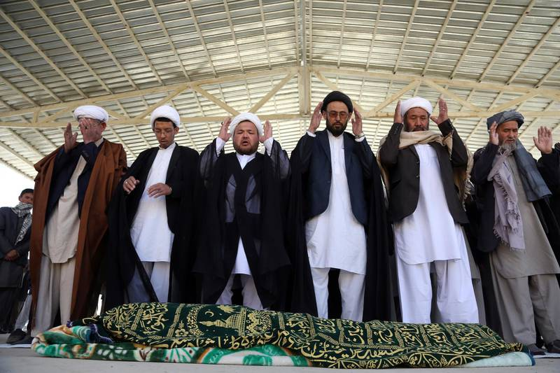 Afghan people offer funeral prayers behind the body of a civilian killed in Sunday's deadly suicide attack at a voter registration center, in Kabul, Afghanistan, Monday, April 23, 2018. Taliban attacks in western Afghanistan killed 14 soldiers and policemen on Monday as residents in the capital, Kabul, prepared for the funerals of those killed in the horrific bombing by the Islamic State group on a voter registration center that left at least 57 dead the previous day. (AP Photo/Rahmat Gul)