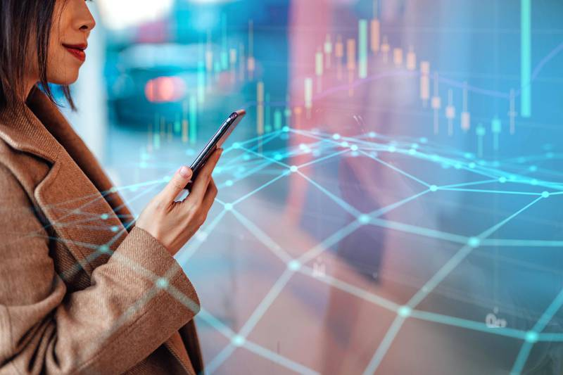 Closeup shot of young woman analysing and checking stock market over smartphone in downtown financial district. Stock exchange market trading board in background. Blockchain concept. Crytocurrency market.
