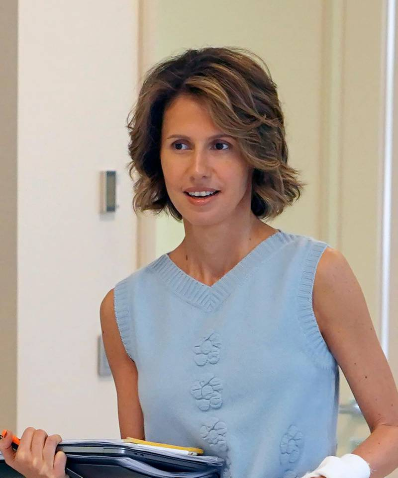 """This handout picture released by the Syrian Presidency Facebook page on August 8, 2018, shows the Syrian First Lady Asma al-Assad carrying papers as she begins treatment for early-stage breast cancer at a hospital in the capital Damascus. (Photo by Handout / Syrian Presidency Facebook page / AFP) / RESTRICTED TO EDITORIAL USE - MANDATORY CREDIT """"AFP PHOTO / Syrian Presidency Facebook page """" - NO MARKETING NO ADVERTISING CAMPAIGNS - DISTRIBUTED AS A SERVICE TO CLIENTS"""