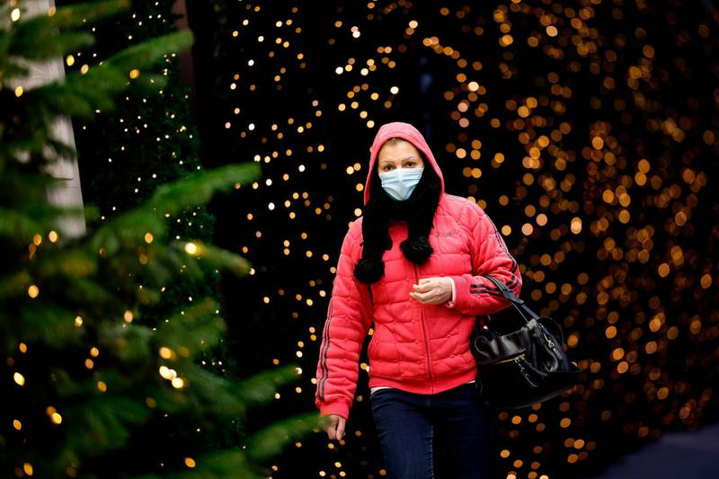 A pedestrian wearing a face mask or covering due to the COVID-19 pandemic, walk past Christmas-themed window display at Selfridges department store in central London on November 17, 2020. Britain has been the worst-hit nation in Europe recording more than 50,000 coronavirus deaths from some 1.2 million positive cases. / AFP / Tolga Akmen