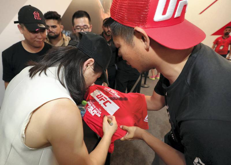Abu Dhabi, United Arab Emirates - September 06, 2019: Fight fans with fighter Zhang Wei Li as she signs a shirt at the UFC fan zone. Friday the 6th of September 2019. Yes Island, Abu Dhabi. Chris Whiteoak / The National