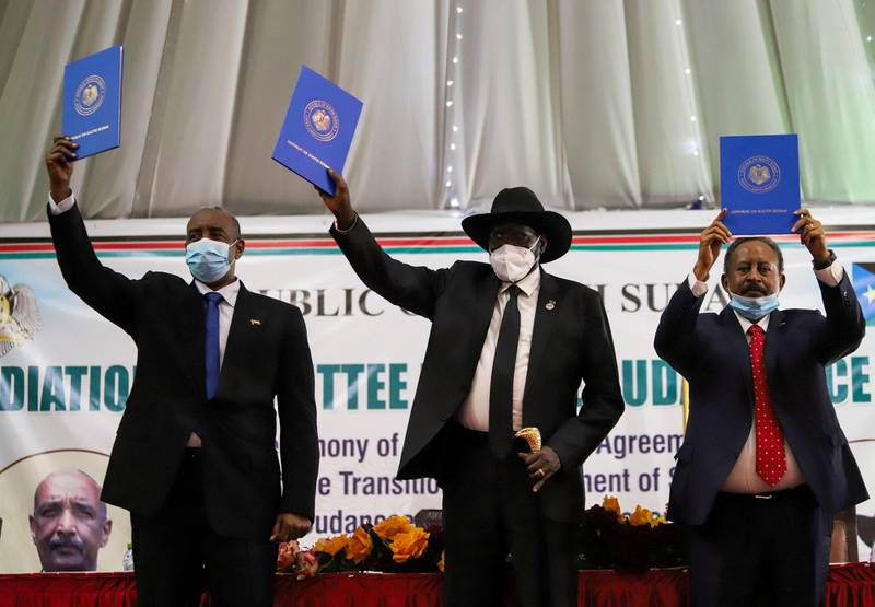 FILE PHOTO: Sudan's Sovereign Council Chief General Abdel Fattah al-Burhan, South Sudan's President Salva Kiir, and Sudan's Prime Minister Abdalla Hamdok lift copies of a signed peace agreement with the country's five key rebel groups, a significant step towards resolving deep-rooted conflicts that raged under former leader Omar al-Bashir, in Juba, South Sudan August 31, 2020. REUTERS/Samir Bol/File Photo