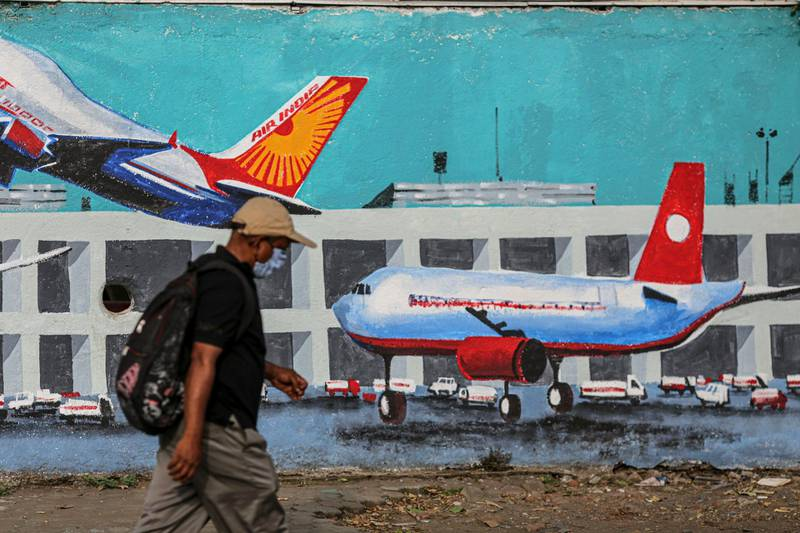 A pedestrian walks past a mural of aircraft at an airport, in Mumbai, India, on Wednesday, May 26, 2021. India is preparing a stimulus package for sectors worst affected by a deadly coronavirus wave, aiming to support an economy struggling with a slew of localized lockdowns, people familiar with the matter said. The finance ministry is working on proposals to bolster the tourism, aviation and hospitality industries, along with small and medium-sized companies. Photographer: Dhiraj Singh/Bloomberg