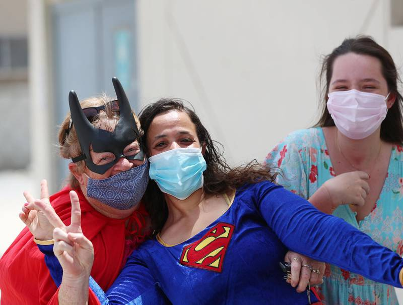 Ibtihal Makmahi-Tarik, Eleanor Jones (R) and Nicky Putter (L). Women dressed as superheroes handed out food, water, toiletries and water bottles at a labour camp in Al Quoz, Dubai on June 25th, 2021. Chris Whiteoak / The National.  Reporter: N/A for News