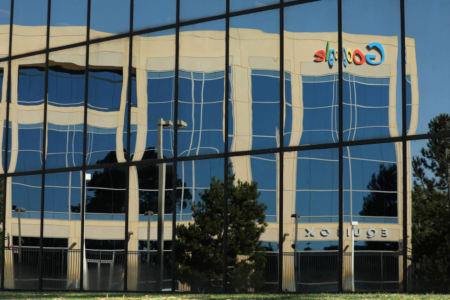 The Google logo is shown reflected on an adjacent office building in Irvine, California, U.S. August 7, 2017.   REUTERS/Mike Blake