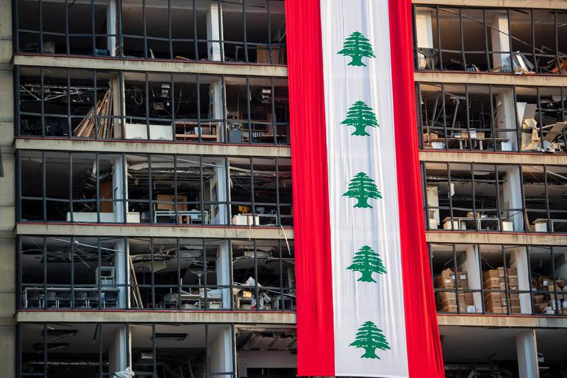 A banner with representations of the Lebanese flag hangs on a damaged building in a neighborhood near the site of last week's explosion that hit the seaport of Beirut, Lebanon, Wednesday, Aug. 12, 2020. (AP Photo/Hassan Ammar)