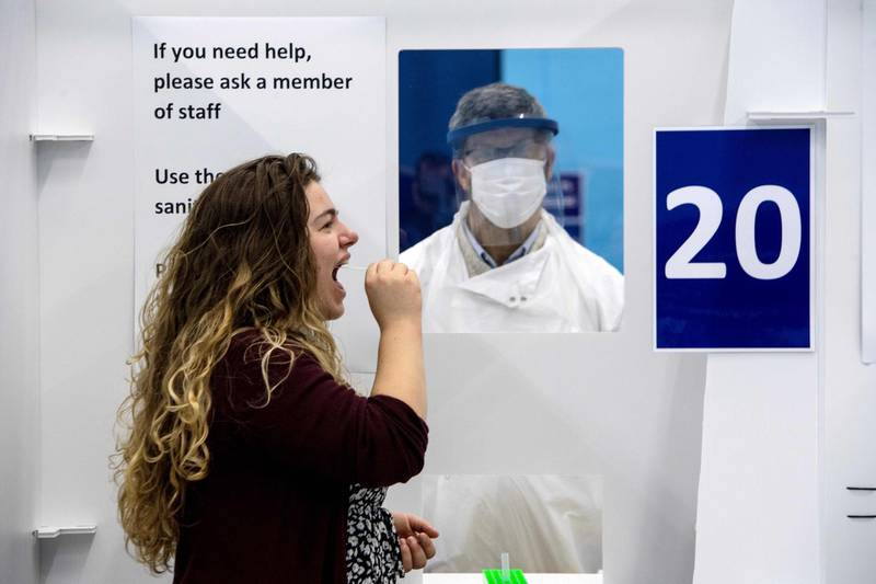 A student from the University of St. Andrews takes a swab for a lateral-flow test in a mass COVID-19 testing centre, set up in the University's sports hall in St. Andrews, eastern Scotland on November 27, 2020, to determine if they are able to travel home for the Christmas break.  / AFP / Andy Buchanan