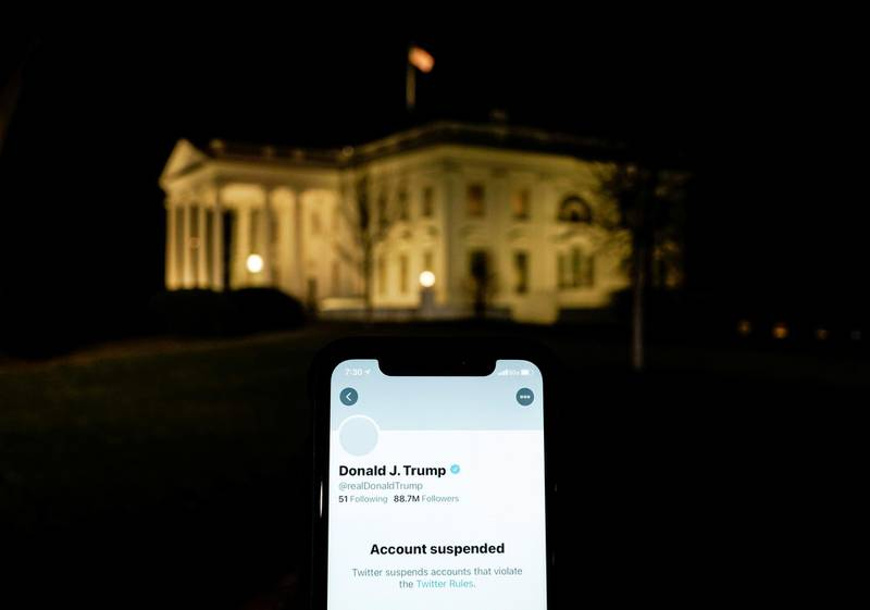 A photo illustration shows the suspended Twitter account of U.S. President Donald Trump on a smartphone and the White House in Washington, U.S., January 8, 2021.  REUTERS/Joshua Roberts/Illustration