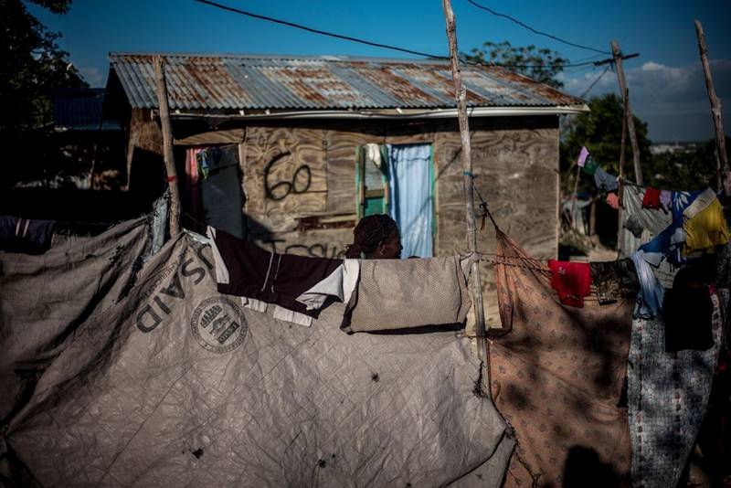 A resident stands behind a fence made of tarp from the U.S. Agency for International Development (USAID) at the Caradeux refugee camp, set up after the 2010 earthquake, in Port-Au-Prince, Haiti, on Tuesday, Jan. 30, 2018. Billions of aid poured in from donors in the years that followed the 2010 earthquake. Yet, the money has done little to address poverty. Haiti PresidentMoise has aimed his strongest criticism at the way foreign aid has been administered in Haiti. Photographer: Alejandro Cegarra/Bloomberg