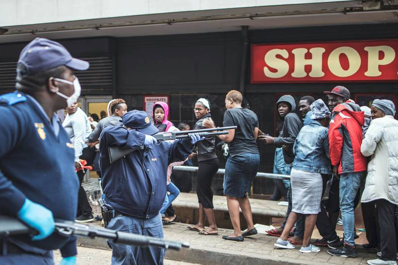 A South African policeman points his pump rifle to disperse a crowd of shoppers in Yeoville, Johannesburg, on March 28, 2020 while trying to enforce a safety distance outside a supermarket amid concern of the spread of COVID-19 coronavirus. - South Africa came under a nationwide lockdown on March 27, 2020, joining other African countries imposing strict curfews and shutdowns in an attempt to halt the spread of the COVID-19 coronavirus across the continent. (Photo by MARCO LONGARI / AFP)