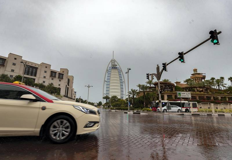 Dubai, United Arab Emirates - Reporter: N/A: Weather. A taxi drives passed the Burj Al Arab as the rain comes down in Dubai. Saturday, March 21st, 2020. Jumeirah, Dubai. Chris Whiteoak / The National