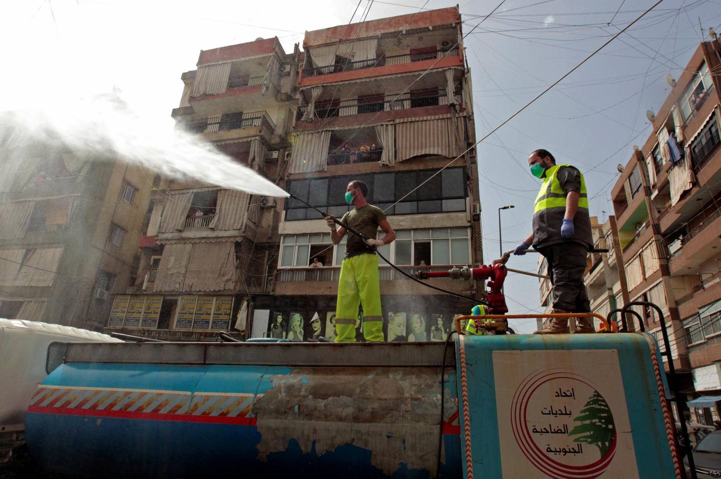 Men stand on a truck as they sanitize a street as a precaution against the spread of coronavirus disease (COVID-19), during a media tour organised by Hezbollah officials, in Beirut's southern suburb, Lebanon March 31, 2020. Picture taken March 31, 2020.  REUTERS/Aziz Taher