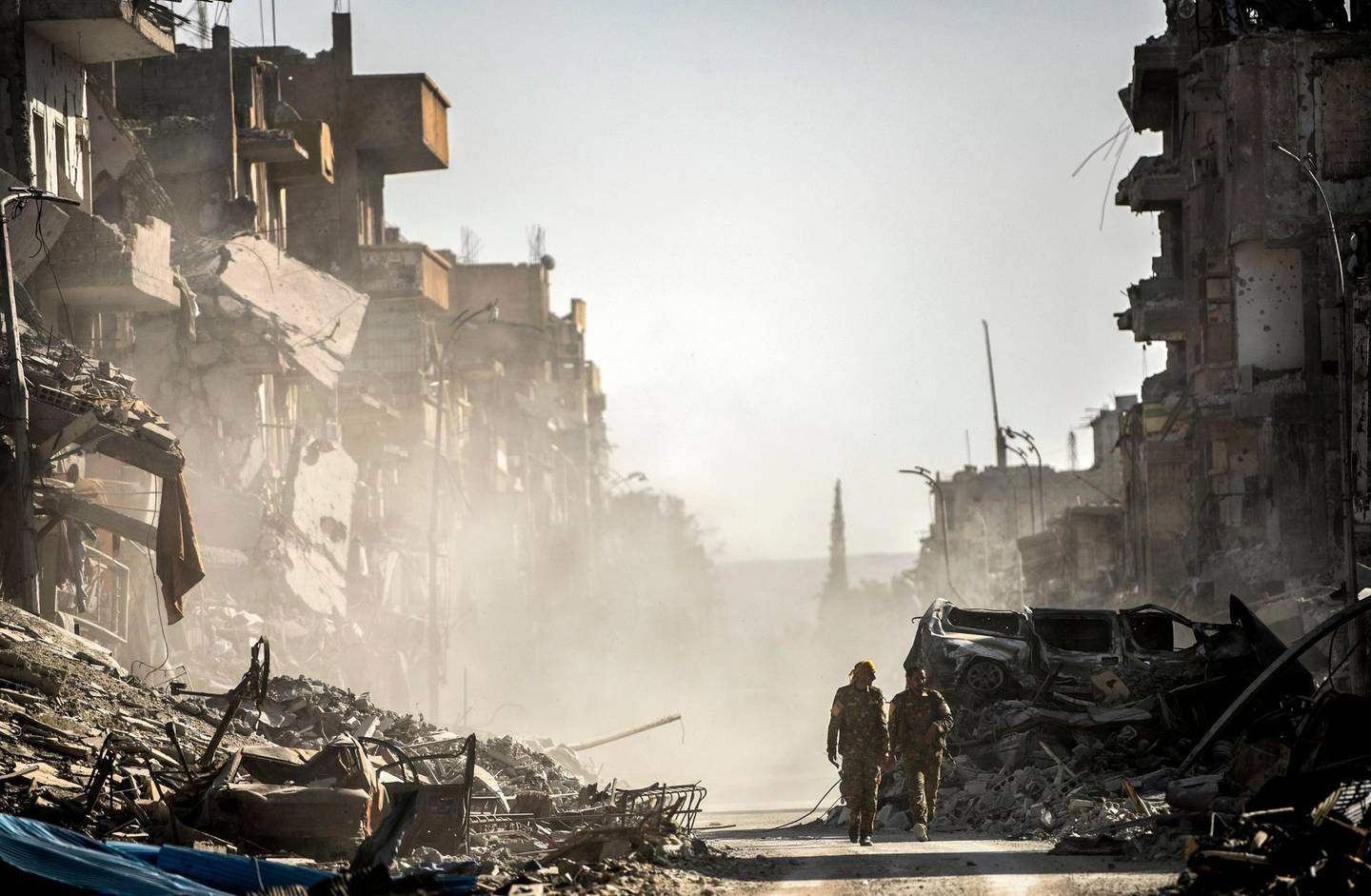"""(FILES) This file photo taken on October 20, 2017 shows fighters of the Syrian Democratic Forces (SDF) walking down a street in Raqa past destroyed vehicles and heavily damaged buildings after a Kurdish-led force expelled Islamic State (IS) group fighters from the northern Syrian city, formerly their """"capital"""". 2017 will be remembered as the year the Islamic State organisation's ultra-violent experiment in statehood was terminated but Iraq and Syria are left staring at ruined cities and daunting challenges. / AFP PHOTO / BULENT KILIC"""