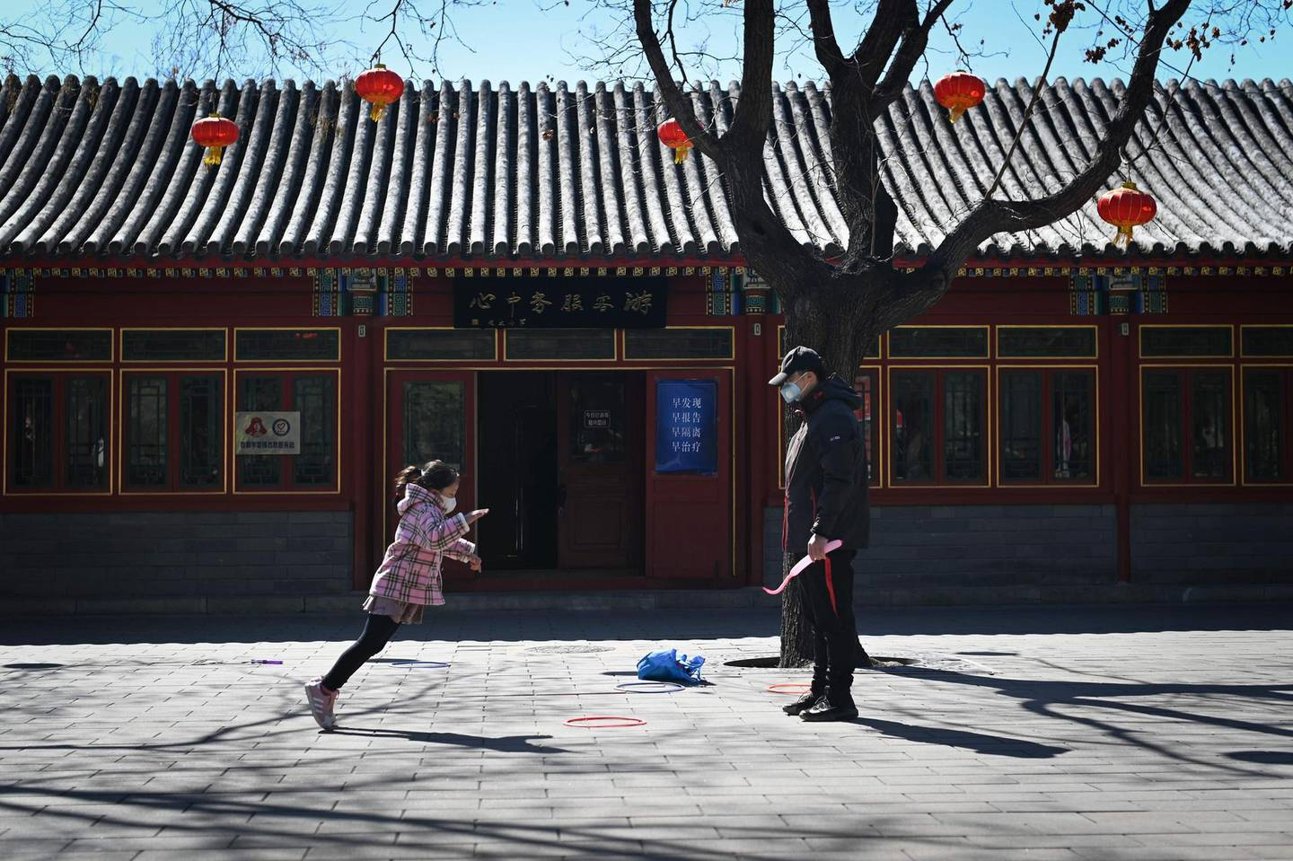 A girl wearing a face mask jumps as she plays with her father in a park in Beijing on March 14, 2020.  China reported 11 new infections of the coronavirus on March 14, and for the first time since the start of the epidemic the majority of them were imported cases from overseas.   / AFP / WANG ZHAO