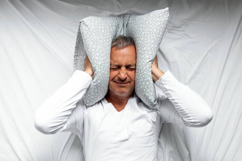 One mature man trying to sleep covering his ears to avoid neighbour noise at home or hotel during the day.