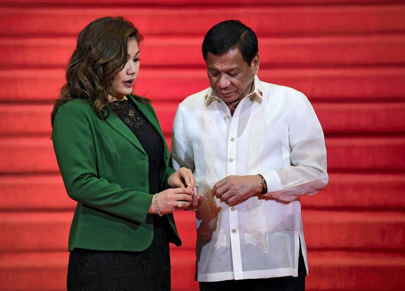 """Philippine President Rodrigo Duterte (R) chats with partner Honeylet Avancena (L) while waiting for leaders to arrive to attend the opening ceremony of the Association of Southeast Asian Nations (ASEAN) leaders' summit in Manila on April 29, 2017. - Southeast Asian countries on April 28 expressed """"grave concern"""" over North Korea's nuclear weapons tests and ballistic missile launches, despite Pyongyang's appeal for support in its tense standoff with the United States. (Photo by MOHD RASFAN / AFP)"""