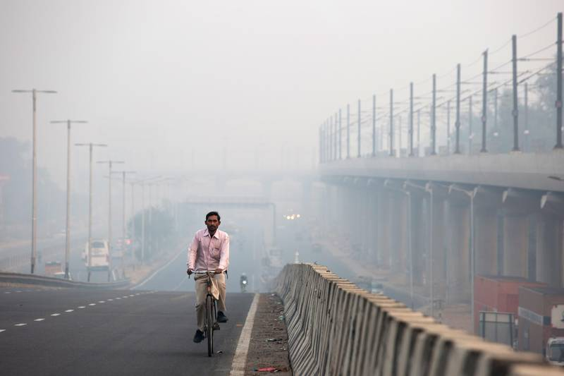A man rides a bicycle along a road shrouded in smog in Delhi, India, on Friday, Nov. 9, 2018. Air pollution levels skyrocketed in New Delhi and left India's capital shrouded in toxic smog as millions of Indians set off firecrackers for Diwali, the Hindu festival of lights. Toxic air is estimated to kill more than 1 million Indians each year, according to the nonprofit Health Effects Institute. Photographer: Ruhani Kaur/Bloomberg