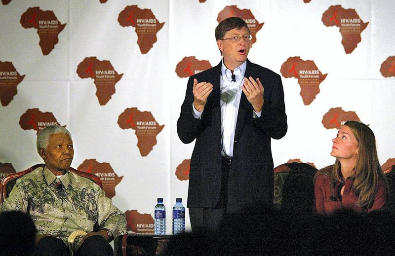 US Microsoft owner Bill Gates (C) addresses a youth forum on HIV/AIDS at the University of Witwatersrand in Johannesburg, 22 September 2003, as his wife Melinda Gates and former South African President Nelson Mandela (L) listen to him. Mandela and Gates took part in the forum that was held to raise awareness of the AIDS epidemic in South Africa. The Bill and Melinda Gates Foundation has already awarded several billion dollars to fund global health projects.       AFP PHOTO / ALEXANDER JOE (Photo by ALEXANDER JOE / AFP)