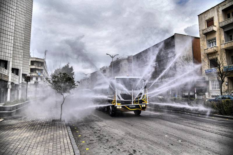 """A handout picture released by the official Syrian Arab News Agency (SANA) on March 20, 2020 shows Syrian Red Crescent vehicles spraying disinfectant along a street in the capital Damascus, as part of measures against the spread of COVID-19 coronavirus disease. (Photo by - / SANA / AFP) / == RESTRICTED TO EDITORIAL USE - MANDATORY CREDIT """"AFP PHOTO / HO / SANA"""" - NO MARKETING NO ADVERTISING CAMPAIGNS - DISTRIBUTED AS A SERVICE TO CLIENTS =="""