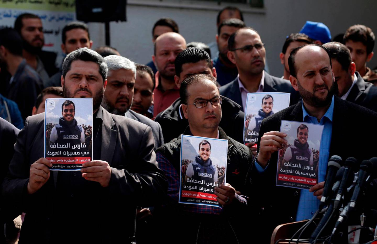 Palestinian journalists carry a portrait of journalist Yasser Murtaja, during his funeral in Gaza City on April 7, 2018. Among those killed at Friday's protest was Yasser Murtaja, a photographer with the Gaza-based Ain Media agency, who died from his wounds after being shot, the local health ministry said.   Murtaja's company confirmed his death, with witnesses saying he was close to the front of the protests in Southern Gaza when he was hit. / AFP PHOTO / MAHMUD HAMS