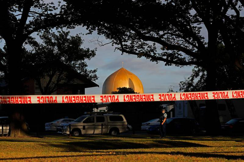 FILE - In this March 17, 2019, file photo,  police officer stands guard in front of the Masjid Al Noor mosque in Christchurch, New Zealand, where one of two mass shootings occurred. A New Zealand man is facing criminal charges after allegedly posting online threats against two Christchurch mosques that were the sites of a terrorist attack that left 51 people dead. Police on Thursday, March 4, 2021, arrested the 27-year-old man and charged him with threatening to kill. If found guilty, he faces a maximum prison sentence of seven years. (AP Photo/Vincent Yu, File)
