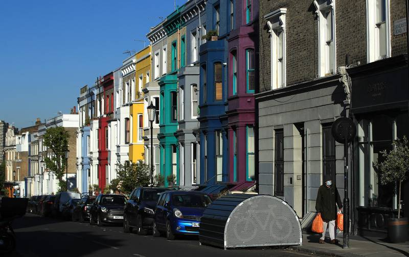 LONDON, ENGLAND  - MAY 15: A person wearing face mask walks past the colourful houses of Notting Hill on May 15, 2020 in London, England. The prime minister announced the general contours of a phased exit from the current lockdown, adopted nearly two months ago in an effort curb the spread of Covid-19. (Photo by Andrew Redington/Getty Images)