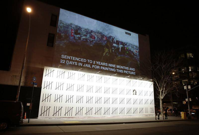 epa06607205 A mural painted by Banksy, the anonymous British street artist, protests the imprisonment of Zehra Dogan on the Bowery in New York City, USA, 15 March 2018. The 70-foot-long mural was unveiled on Thursday, and it protests the imprisonment of the Turkish artist and journalist Zehra Dogan, who was sentenced last March for painting the destruction of a Turkish town, with the country's flag flying over rubble.  EPA-EFE/JASON SZENES