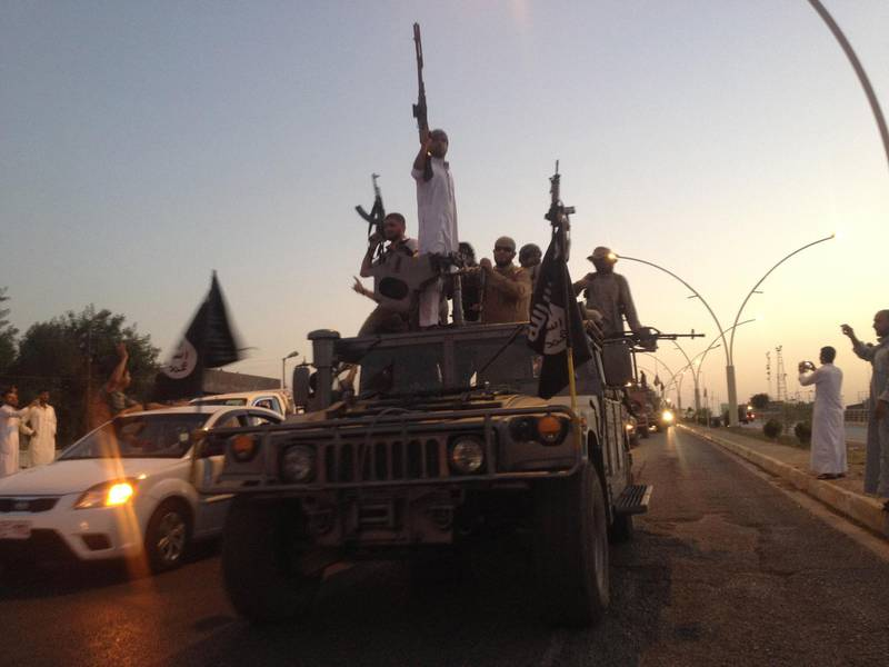 In this photo taken Monday, June 23, 2014, fighters of the al-Qaida-inspired Islamic State of Iraq and the Levant (ISIL) parade in a commandeered Iraqi security forces armored vehicle down a main road at the northern city of Mosul, Iraq, more than two weeks after ISIL took over the country's second largest city. U.S. Secretary of State John Kerry warned Mideast nations on Wednesday against taking new military action in Iraq that might heighten already-tense sectarian divisions, as reports surfaced that Syria launched airstrikes across the border and Iran has been flying surveillance drones over the neighboring country. (AP Photo)