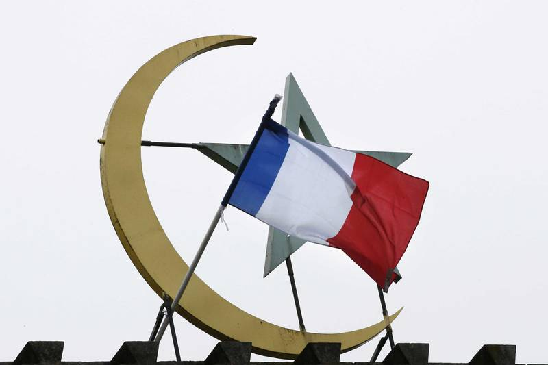 """A French national flag is flown on top of the Grand Mosque of Paris, in Paris on November 27, 2015  in memory of the 130 victims of the November 13, 2015 coordinated terror attacks in Paris claimed by the Islamic State group (IS). A solemn ceremony was held for the victims of the Paris attacks, with President Francois Hollande vowing that France would respond to the """"army of fanatics"""" with more songs, concerts and shows. """"We will not give in either to fear or to hate,"""" said Hollande in the courtyard of the Invalides buildings in central Paris, speaking to 2,000 dignitaries and those injured in the violence. (Photo by PATRICK KOVARIK / AFP)"""