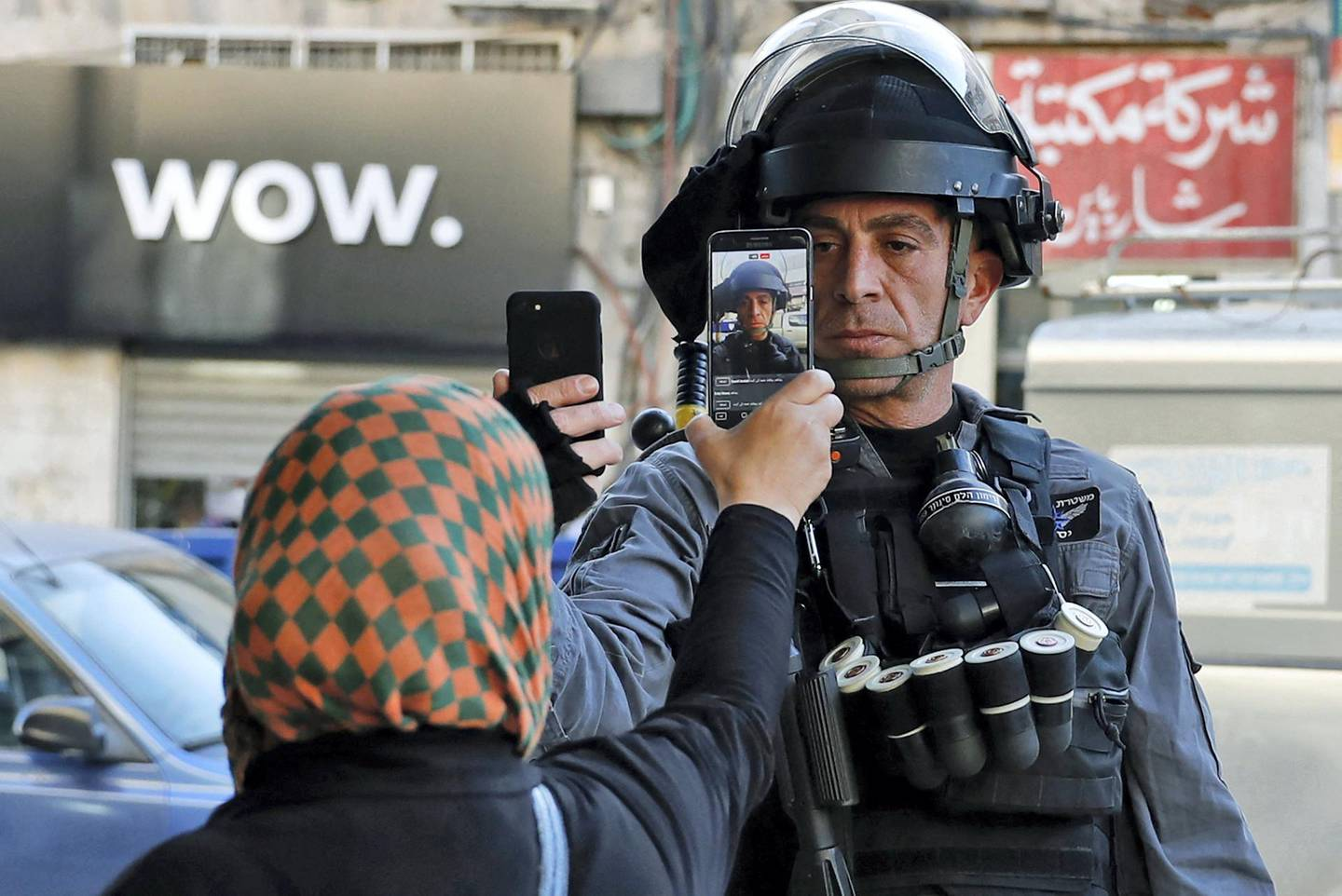 A Palestinian woman takes a picture of a member of the Israeli security forces as he takes her picture in a street in Jerusalem on December 16, 2017, as demonstrations continue to flare in the Middle East and elsewhere over the US president's declaration of Jerusalem as Israel's capital. (Photo by AHMAD GHARABLI / AFP)