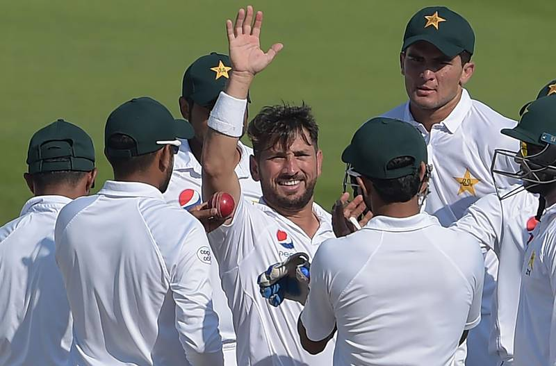 Pakistani spinner Yasir Shah (C) celebrates with teammates after breaking the fastest to 200 Test wickets record during the fourth day of the third and final Test cricket match between Pakistan and New Zealand at the Sheikh Zayed International Cricket Stadium in Abu Dhabi on December 6, 2018. / AFP / AAMIR QURESHI