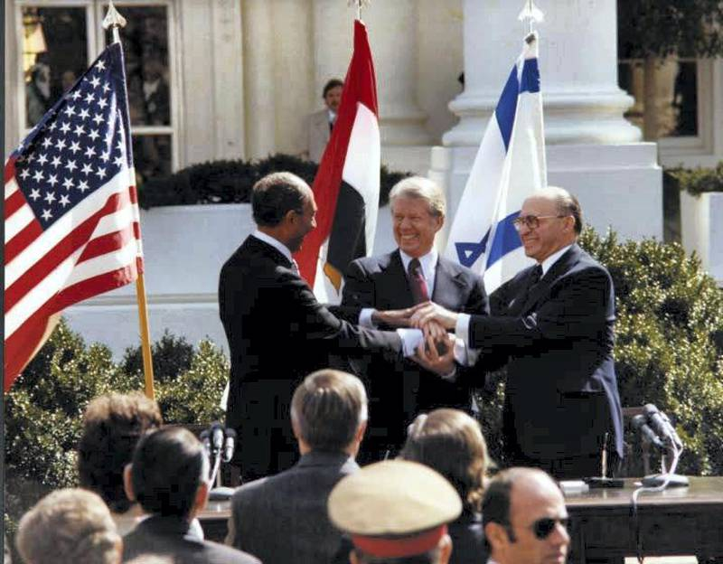U.S. President Jimmy Carter, Egyptian President Anwar Sadat and Israeli Prime Minister Menachem Begin join hands in celebration of the signing of the ÒTreaty of Peace Between the Arab Republic of Egypt and the State of IsraelÓ at the White House in Washington, D.C., March 26, 1979.    Courtesy Jimmy Carter Library/National Archives/Handout via REUTERS    ATTENTION EDITORS - THIS IMAGE WAS PROVIDED BY A THIRD PARTY