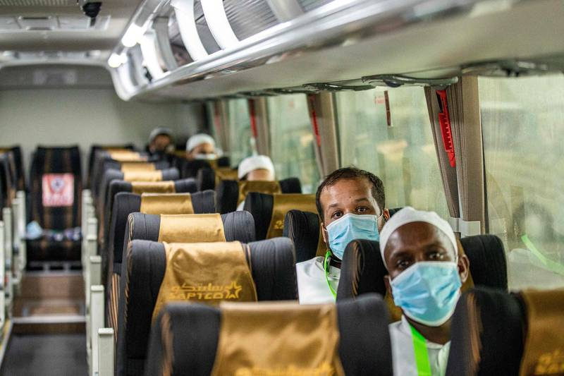 """A handout picture provided by the Saudi Ministry of Hajj and Umra on July 25, 2020, shows travellers among the first group of arrivals for the annual Hajj pilgrimage, mask-clad and seated distantly from one another due to the COVID-19 coronavirus pandemic, riding on a bus transporting them from the Red Sea coastal city of Jeddah's King Abdulaziz International Airport. The 2020 hajj season, which has been scaled back dramatically to include only around 1,000 Muslim pilgrims as Saudi Arabia battles a coronavirus surge, is set to begin on July 29. Some 2.5 million people from all over the world usually participate in the ritual that takes place over several days, centred on the holy city of Mecca. This year's hajj will be held under strict hygiene protocols, with access limited to pilgrims under 65 years old and without any chronic illnesses. - === RESTRICTED TO EDITORIAL USE - MANDATORY CREDIT """"AFP PHOTO / HO / MINISTRY OF HAJJ AND UMRA"""" - NO MARKETING NO ADVERTISING CAMPAIGNS - DISTRIBUTED AS A SERVICE TO CLIENTS ===  / AFP / Saudi Ministry of Hajj and Umra / - / === RESTRICTED TO EDITORIAL USE - MANDATORY CREDIT """"AFP PHOTO / HO / MINISTRY OF HAJJ AND UMRA"""" - NO MARKETING NO ADVERTISING CAMPAIGNS - DISTRIBUTED AS A SERVICE TO CLIENTS ==="""